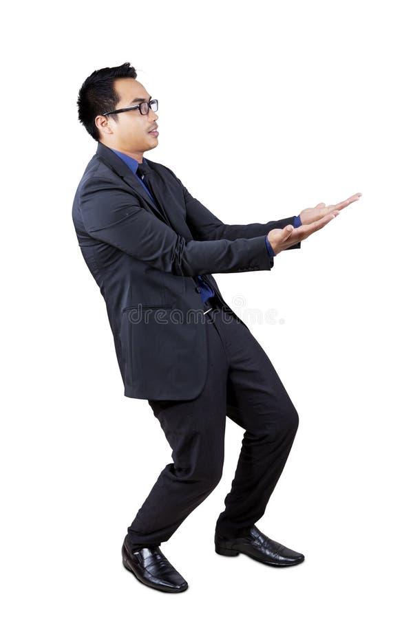 Geschäftsmann, der etwas im Studio trägt stockfotos