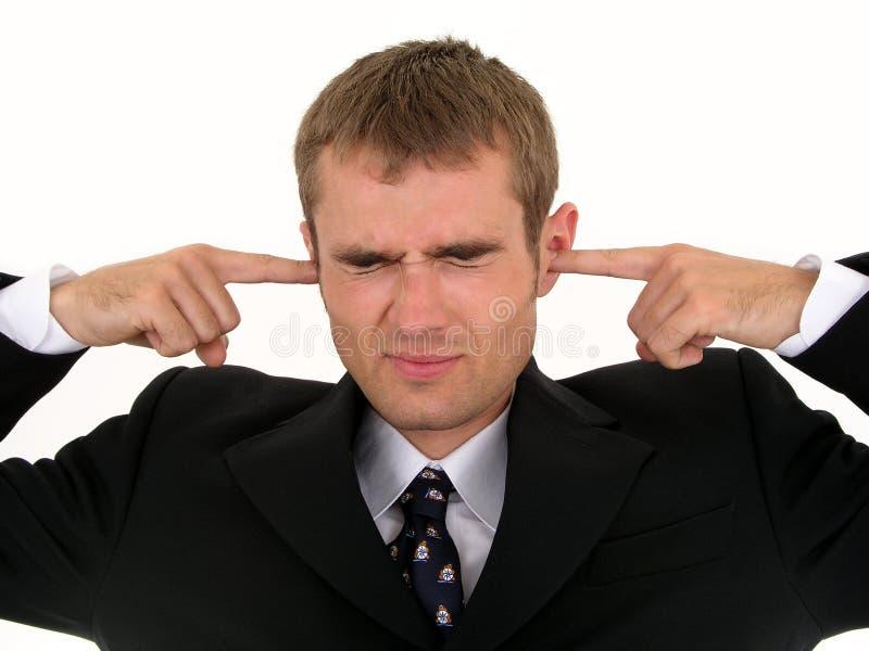 Geschäftsmann, der Finger in Ohren einsetzt lizenzfreie stockfotos