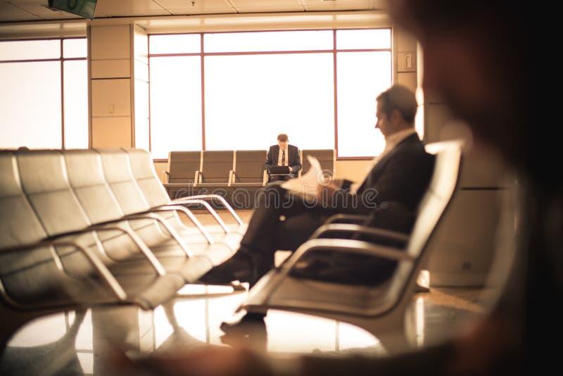 Geschäftsmann, der am Flughafen, seinen Flug wartend sitzt lizenzfreie stockfotografie