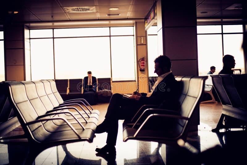 Geschäftsmann, der am Flughafen wartet seinen Flug sitzt lizenzfreie stockfotos