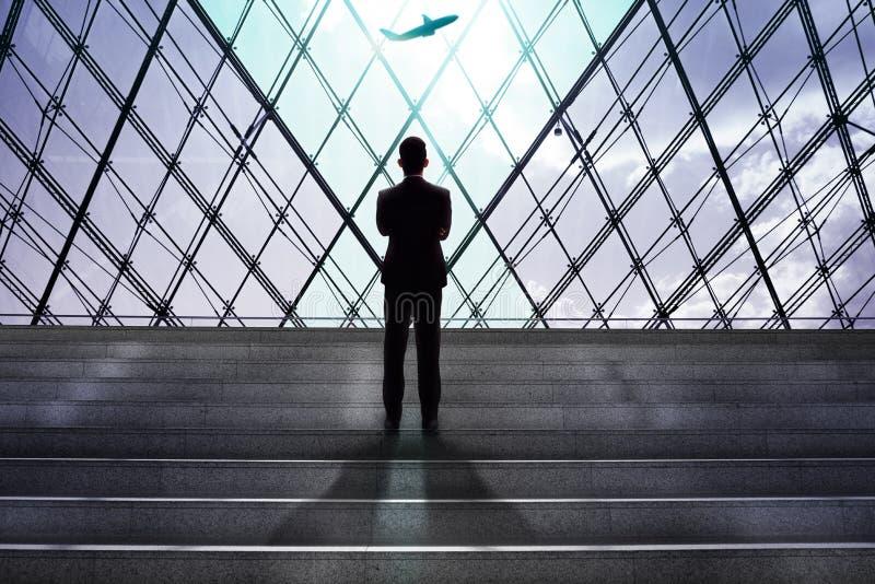 Geschäftsmann, der Flugzeug-Einstieg in Flughafen-Abfahrt g betrachtet lizenzfreie stockbilder