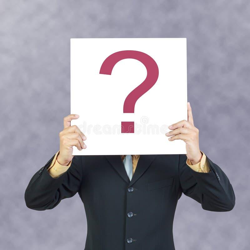 Geschäftsmann, der Fragenzeichen hält lizenzfreies stockbild