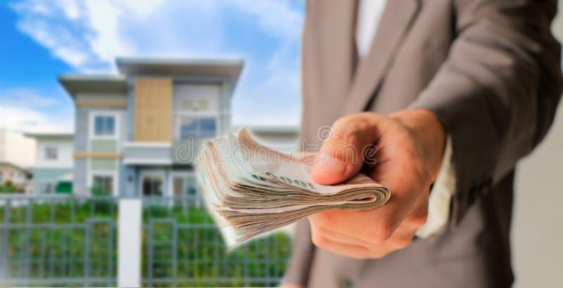 Geschäftsmann, der Geld mit unscharfem Haus gibt stockfotos
