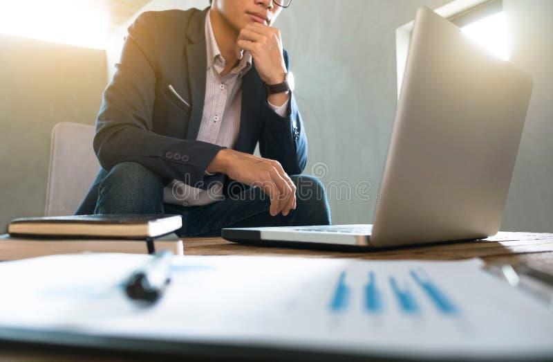 Geschäftsmann, der an Geschäftsdokument und Laptop an einem Arbeitsplatz arbeitet stockfotos