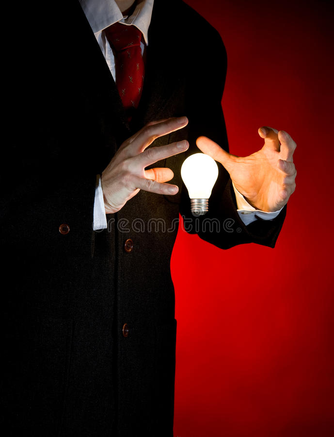 Geschäftsmann, der Glühlampe anhält stockfotos