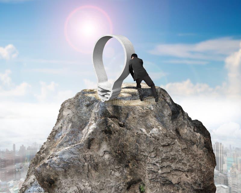 Geschäftsmann, der Glühlampe auf Eurozeichenentwurfsbergspitze drückt lizenzfreies stockbild