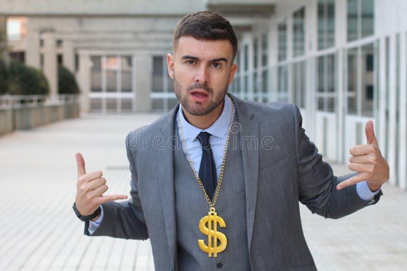 Geschäftsmann, der goldene Halskette mit Dollarzeichen schaukelt stockfotos