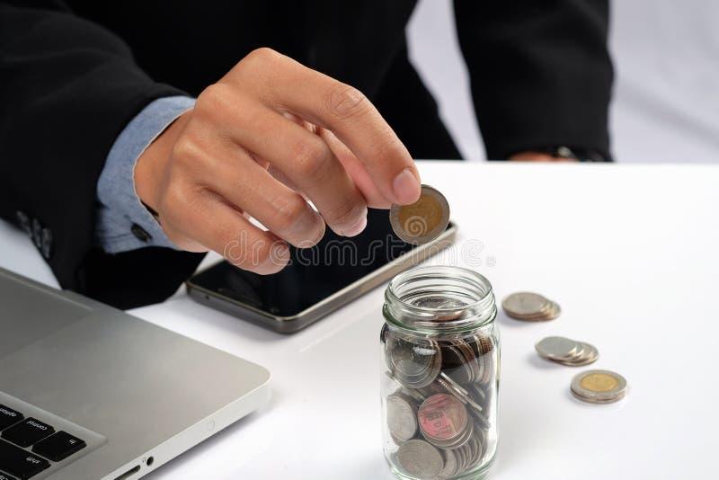 Geschäftsmann, der goldene Münzen in Flasche einsetzt stockbild