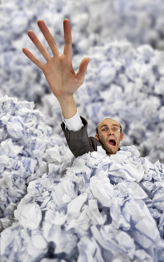Geschäftsmann, der in großen Haufen der zerknitterten Papiere sinkt lizenzfreie stockbilder