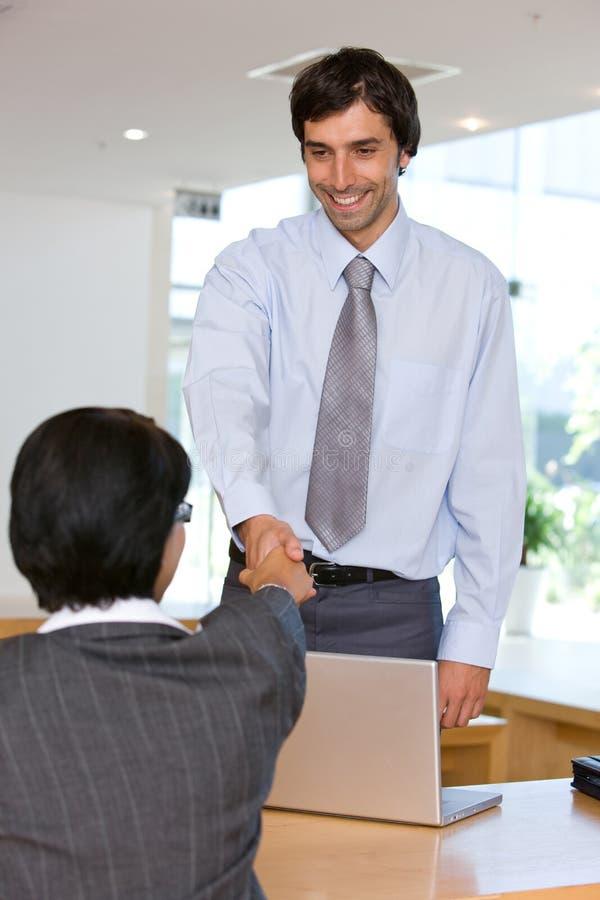 Geschäftsmann, der Hände mit Klienten rüttelt stockbild