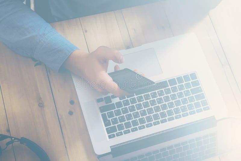 Geschäftsmann, der am hölzernen Tisch mit Laptop arbeitet Männliche Hand, die Smartphone hält Beschneidungspfad eingeschlossen Ho lizenzfreie stockfotos