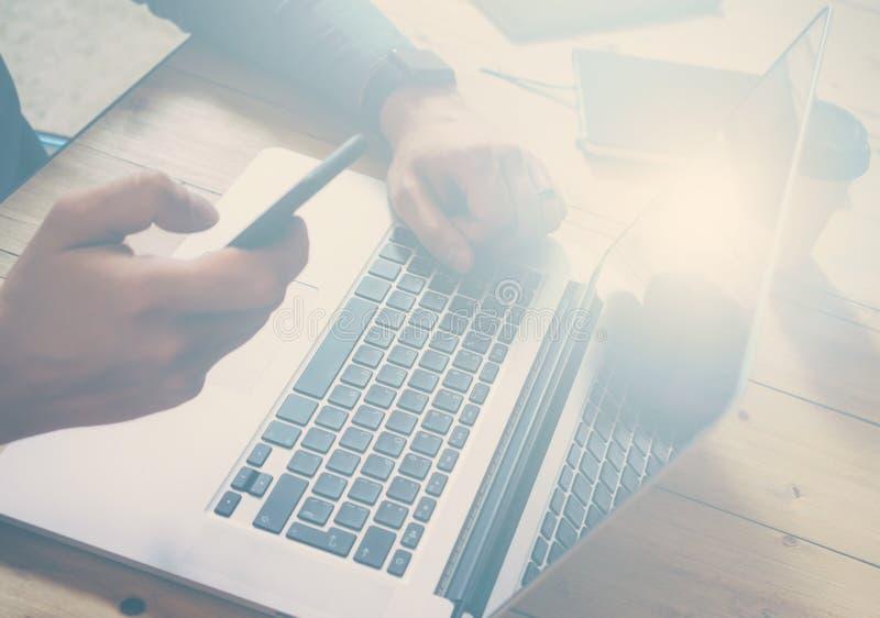 Geschäftsmann, der am hölzernen Tisch mit Laptop arbeitet Mann, der Smartphone und simsende Mitteilung zur Hand hält Horizontal,  lizenzfreie stockbilder