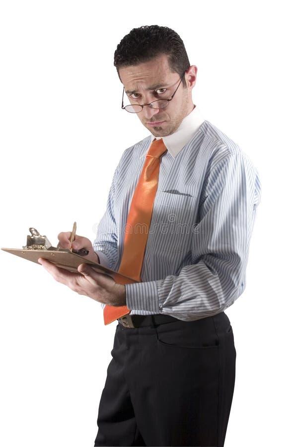 Geschäftsmann, der an Hand über seinen Gläsern mit Klemmbrett - Franc schaut lizenzfreie stockfotografie