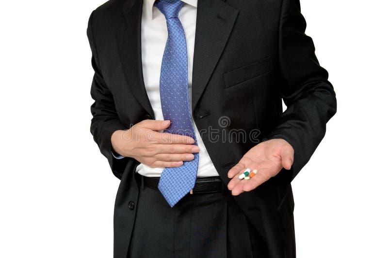Geschäftsmann, der in der Hand Pille hält und Bauchschmerzen hält stockfotos