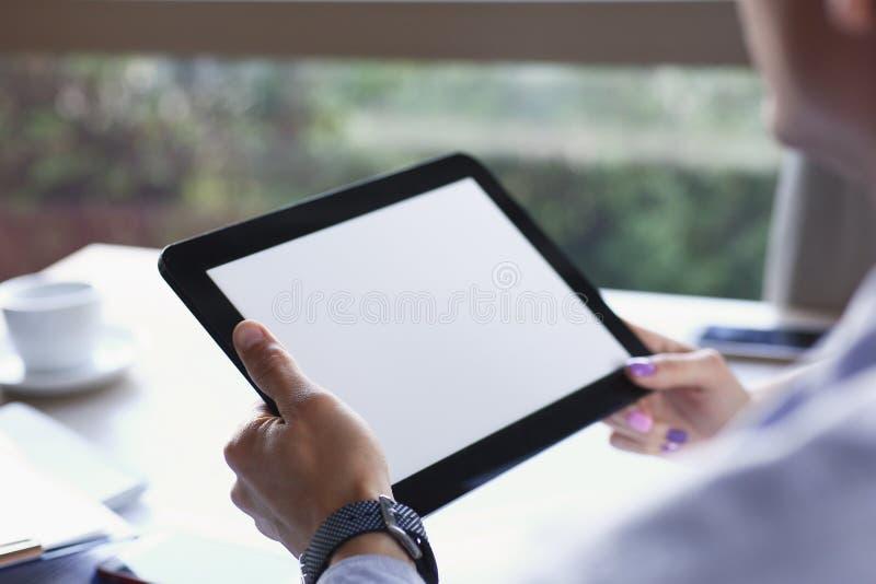 Geschäftsmann, der in der Hand Tablette im Café hält lizenzfreie stockbilder