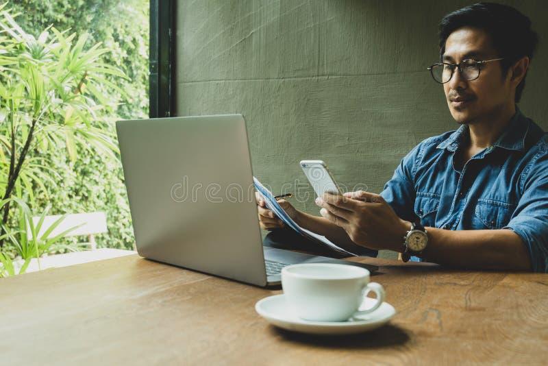 Geschäftsmann, der Handy betrachtet und Schreibarbeit mit Laptop auf Tabelle hält stockfoto