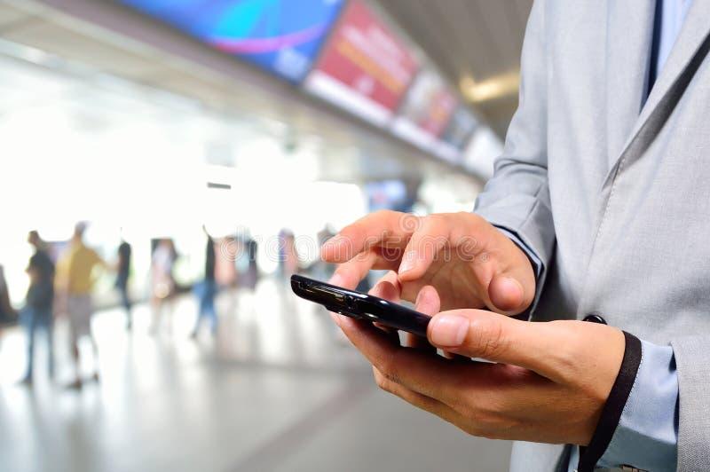 Geschäftsmann, der Handy in der modernen Bahnstation verwendet stockbild