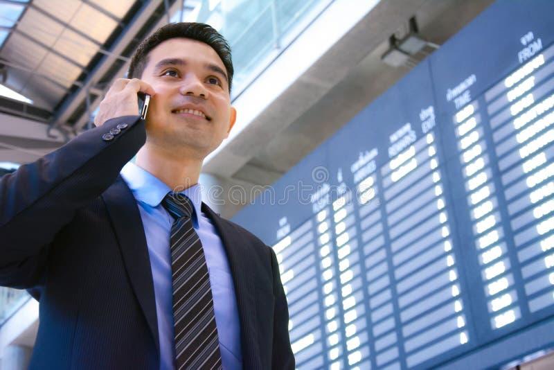 Geschäftsmann, der am Handy innerhalb des Flughafenabfertigungsgebäudes spricht stockfoto