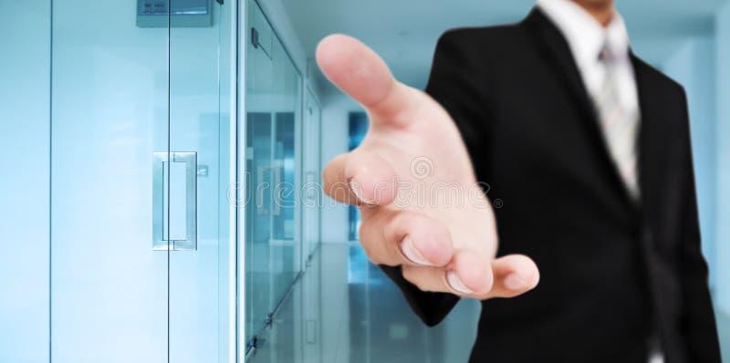 Geschäftsmann, der heraus Hand mit blauem modernem Bürohintergrund, Geschäftswillkommen, Zeichen und Partnerschaft mit cooperati  lizenzfreie stockfotografie