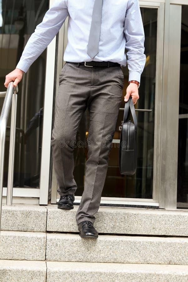Geschäftsmann, der heraus vom Büro nach Arbeitstag und Holding ein lederner Aktenkoffer in seiner Hand geht stockfotografie