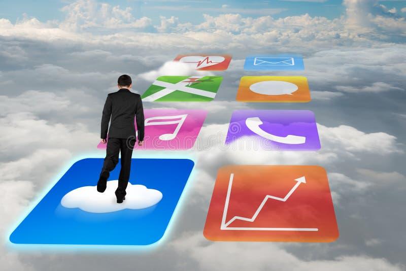 Geschäftsmann der hinteren Ansicht, der auf glänzende APP-Ikonen mit cloudscape surft stock abbildung