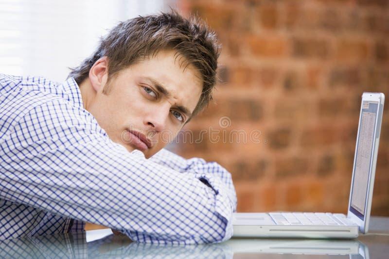 Geschäftsmann, der im Büro mit Laptop sitzt stockfotos