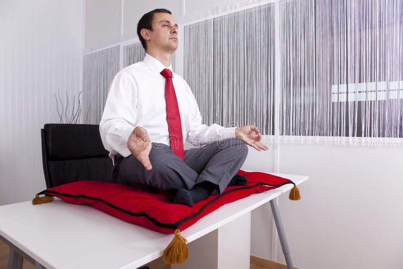 Geschäftsmann, der im Büro sich entspannt lizenzfreie stockfotos