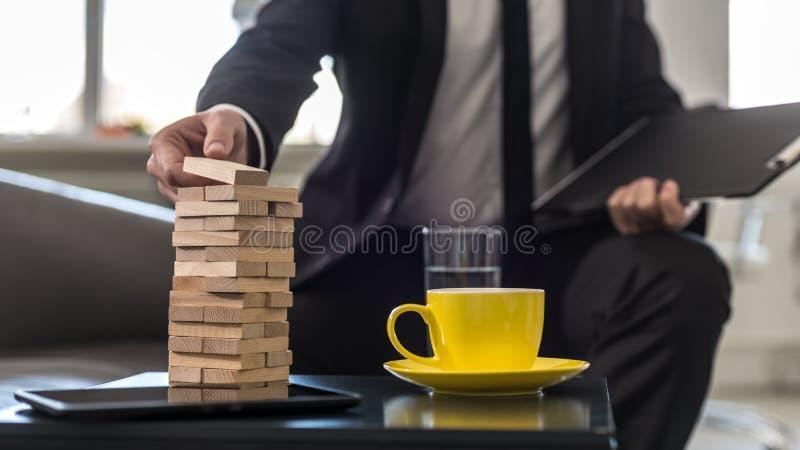 Geschäftsmann, der im Bürogebäude einen Turm von Staplungsblöcken sitzt stockfotos