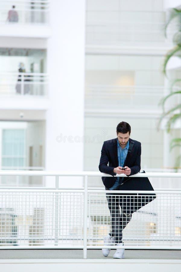 Geschäftsmann, der im Bürogebäude steht lizenzfreie stockbilder