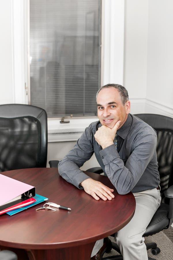 Geschäftsmann, der im BüroKonferenzzimmer sitzt lizenzfreies stockfoto