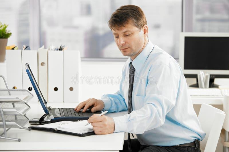 Geschäftsmann, der im persönlichen Organisator sucht stockfotografie