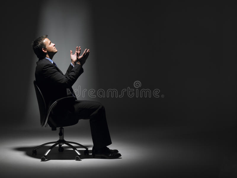 Geschäftsmann, der im Scheinwerfer sitzt stockfotografie