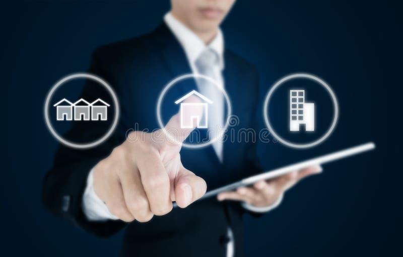 Geschäftsmann, der Immobilienikonen auf Schirm bedrängt Anlagengeschäft in den Immobilien, im Reihenhaus, im Einzelnen Haus und i lizenzfreie stockbilder