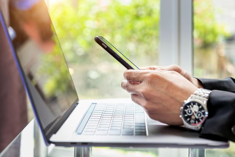 Geschäftsmann, der intelligentes Telefon verwendet und oben an Laptop, Abschluss von Händen des Geschäftsmannes, Geschäftskonzept stockbild
