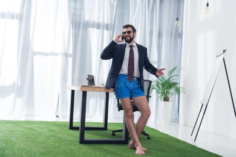 Geschäftsmann in der Jacke und kurze Hosen, die auf Smartphone am Arbeitsplatz sprechen lizenzfreie stockfotografie