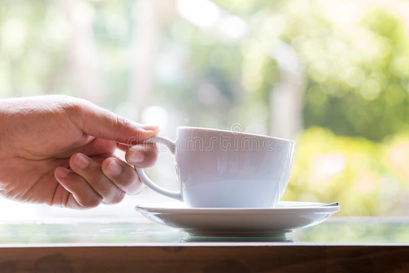Geschäftsmann, der Kaffeetasse für das Trinken im Kaffeecafé nimmt stockbild