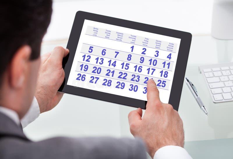 Geschäftsmann, der Kalender auf digitaler Tablette betrachtet lizenzfreie stockbilder
