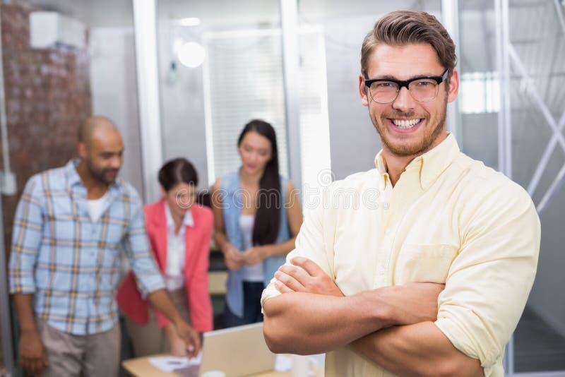 Geschäftsmann, der an der Kamera mit Arme crosse lächelt stockbilder