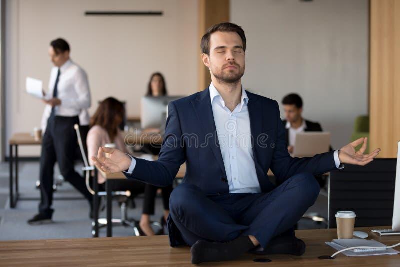 Geschäftsmann in der Klage, die auf Tabelle sitzt und im Büro meditiert stockfoto