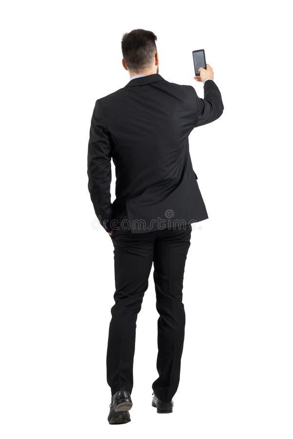 Geschäftsmann in der Klage, die nach hinterer Ansicht des guten Telefonsignals sucht oder Foto macht stockfoto