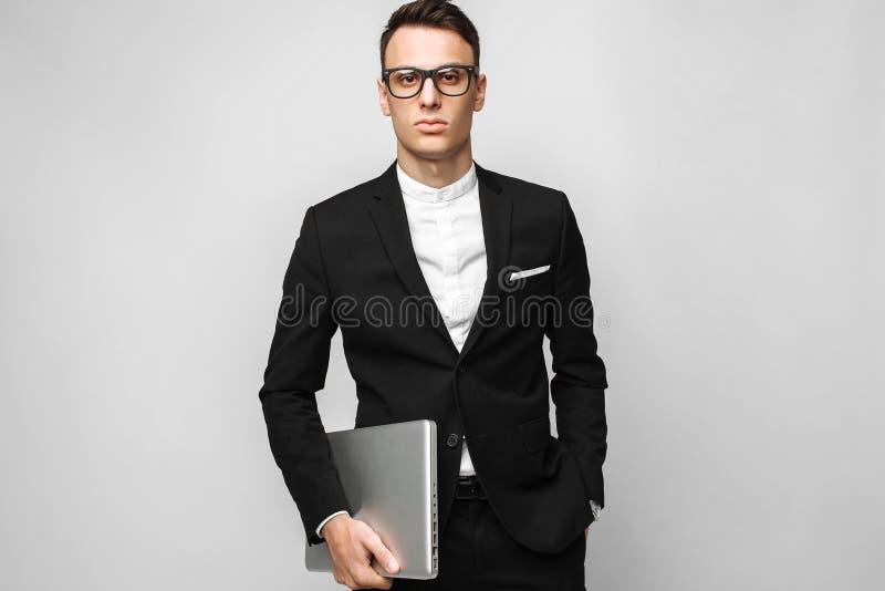 Geschäftsmann in der Klage und Gläser mit dem Laptop lokalisiert auf grauem Ba lizenzfreie stockfotos
