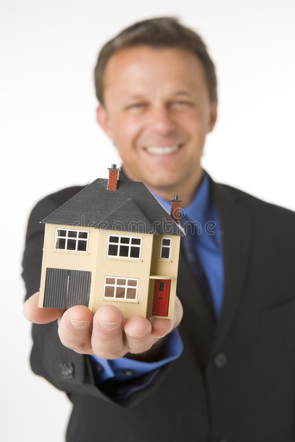 Geschäftsmann, der kleines Haus anhält stockfotos
