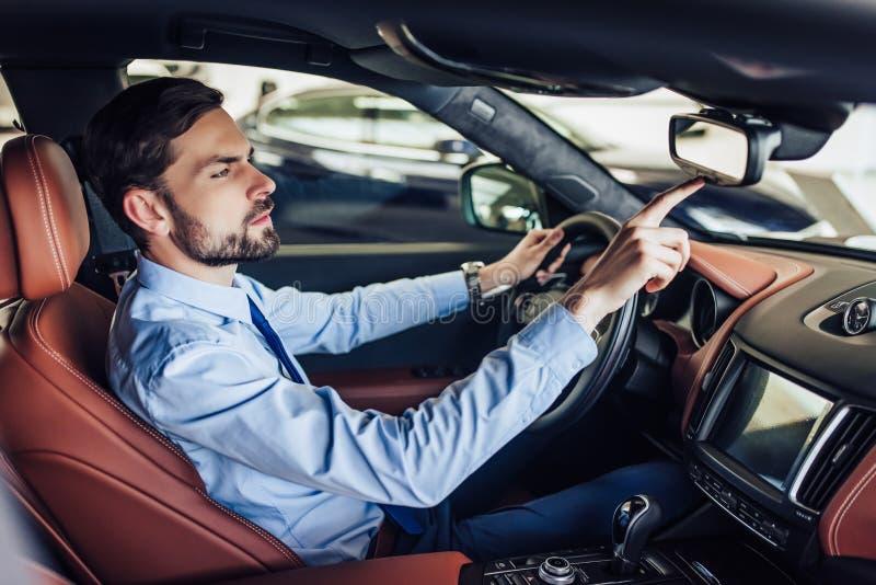 Geschäftsmann, der Knopf auf dem Rückspiegel im Auto betätigt lizenzfreies stockbild