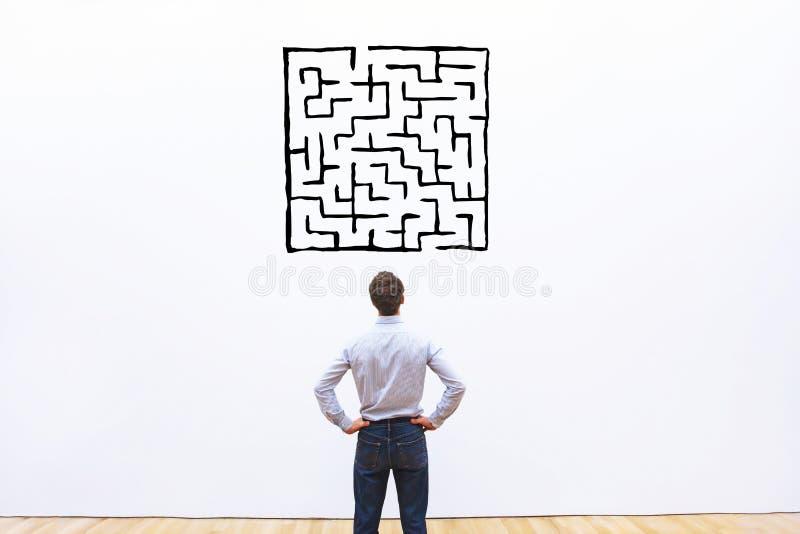 Geschäftsmann, der Labyrinthzeichnung betrachtet lizenzfreies stockbild