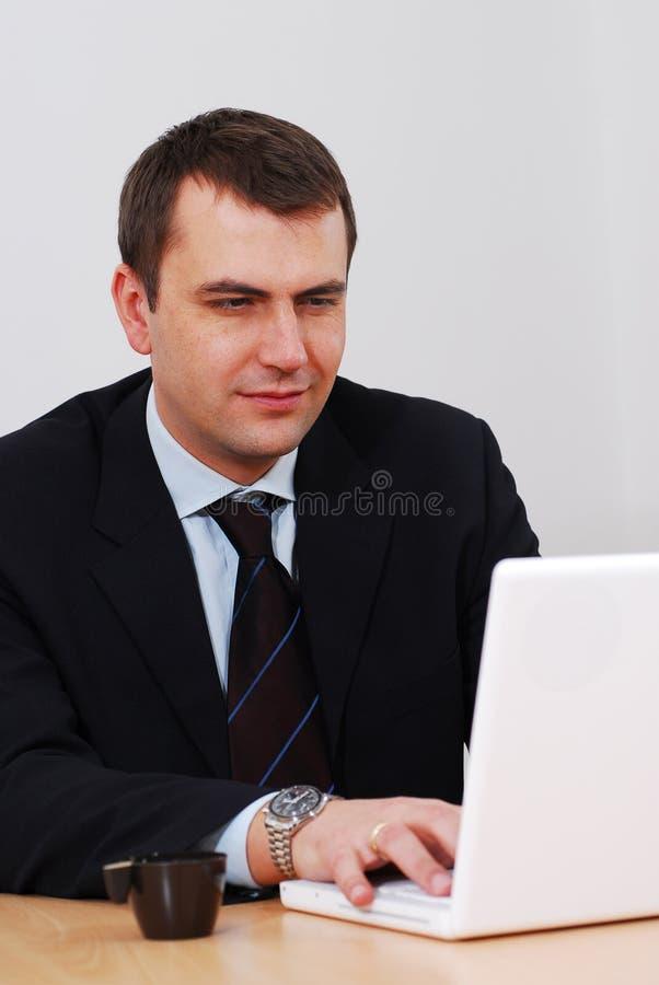 Geschäftsmann, der an Laptop arbeitet stockfoto