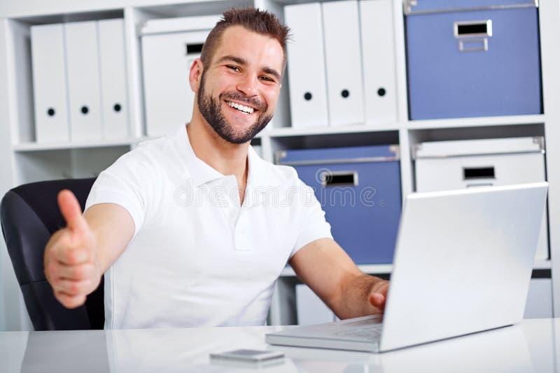 Geschäftsmann, der an Laptop arbeitet und die okaygeste macht stockbild