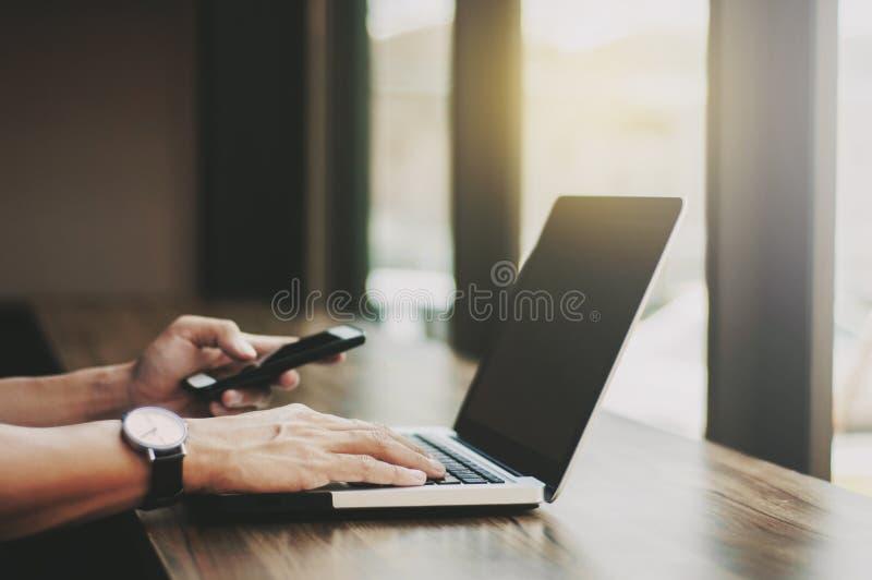Geschäftsmann, der an Laptop arbeitet und intelligentes Mobiltelefon am Arbeitsplatz verwendet lizenzfreie stockfotografie