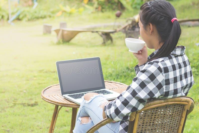 Geschäftsmann, der an Laptop-Computer und trinkendem Kaffee in t arbeitet stockfoto