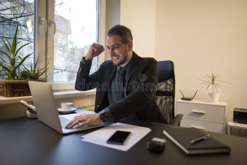 Geschäftsmann, der an Laptop im Büro zufriedengestellt mit Ergebnissen arbeitet lizenzfreie stockbilder