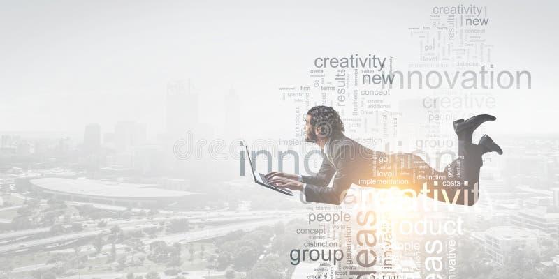 Geschäftsmann, der am Laptop mit Geschäftstextcollage auf weichem Hintergrund des Stadtbilds liegt und arbeitet stockfoto